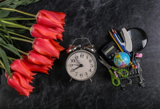 Bukiet tulipanów i wózek na zakupy z przyborami szkolnymi na tablicy kredowej. wiedza, dzień nauczyciela, powrót do szkoły. widok z góry