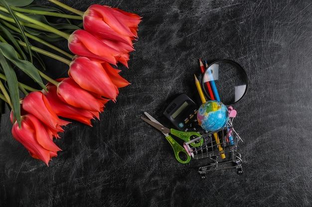 Bukiet tulipanów i wózek na zakupy z przyborami szkolnymi na tablicy kredowej. wiedza, dzień nauczyciela, powrót do szkoły