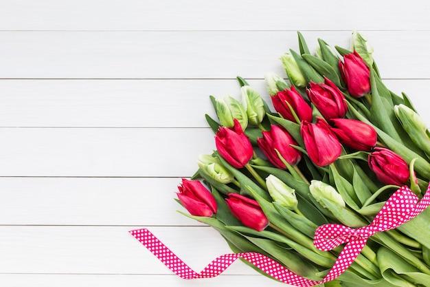 Bukiet tulipanów na białej drewnianej ścianie.