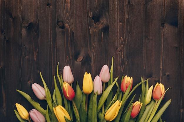 Bukiet tulipanów na ciemnym tle drewniane. leżał płasko, widok z góry z lato, rustykalny styl.