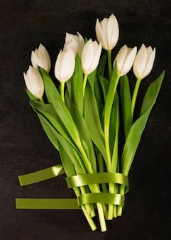 Bukiet tulipanów na czarnym tle.