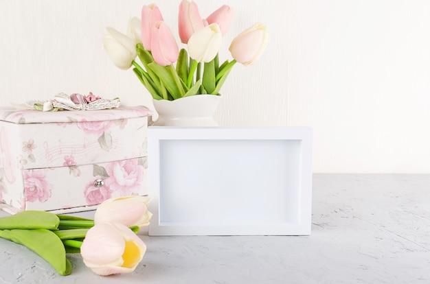 Bukiet tulipanów pastelowych w ceramicznym dzbanku z pustą białą ramką na półce