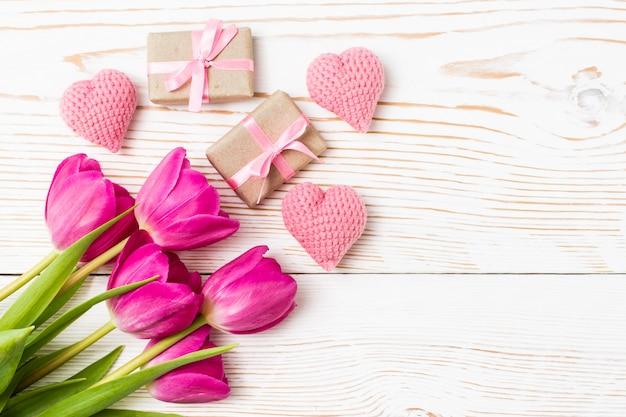 Bukiet tulipanów, prezenty i serca na białym drewnie, widok z góry