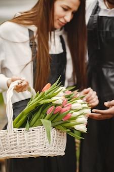 Bukiet tulipanów u faceta. facet i dziewczyna w szklarni. g. utwardzacze w fartuchach.