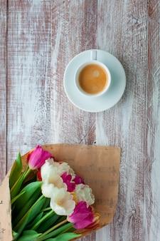 Bukiet tulipanów zawinięty jest w papier na białym tle na tle drewna