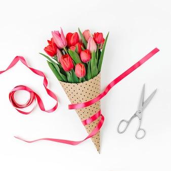Bukiet tulipanów, zawinięty w papier i ozdobiony wstążką