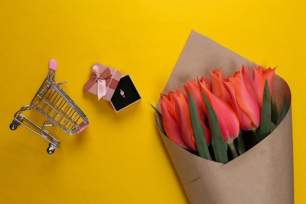 Bukiet tulipanów, złoty pierścionek z brylantem w upominkowym pudełku, wózek z supermarketu na żółto