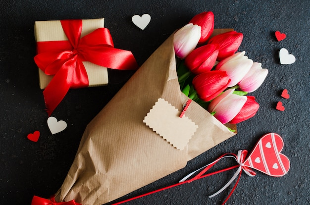 Bukiet tulipany i prezenta pudełko na ciemnym tle.