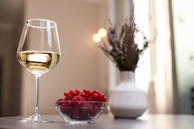 Bukiet w wazonie, kieliszek białego wina i świeżych malin na stole na tarasie