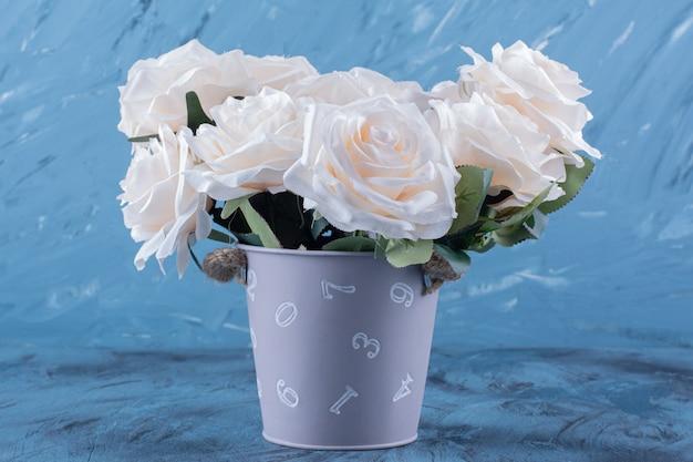 Bukiet wielu białych róż umieszczonych na niebiesko.