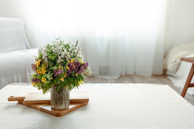 Bukiet wiosennych kwiatów jako detal dekoracyjny we wnętrzu pomieszczenia.