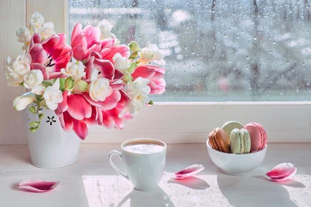 Bukiet wiosennych kwiatów: różowe tulipany i biała frezja. różowe i zielone makaroniki, smaczne słodycze do espresso. filiżanka kawy na desce okna, słońce po deszczu.