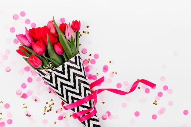 Bukiet wiosennych kwiatów tulipanów i konfetti. układ płaski, widok z góry
