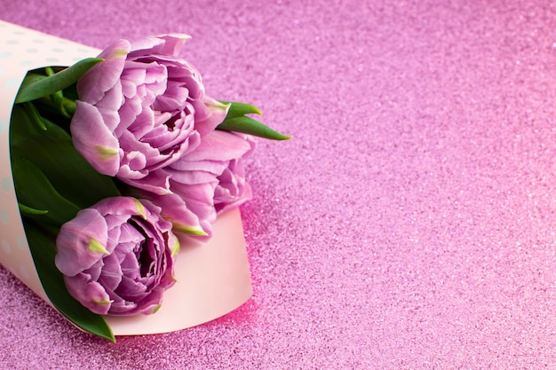 Bukiet wiosennych tulipanów bzu i miejsce na tekst na dzień matki lub 8 marca na powierzchni z różowym brokatem płaski widok z góry