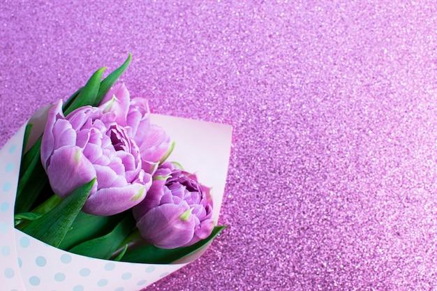 Bukiet wiosennych tulipanów bzu na liliowej brokatowej powierzchni