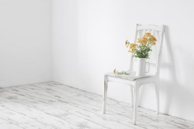Bukiet wrotyczu pospolitego na starym drewnianym krześle w białym wnętrzu