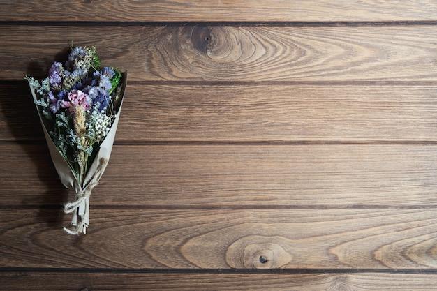 Bukiet wysuszeni dzicy kwiaty na nieociosanym drewnianym stołowym tle
