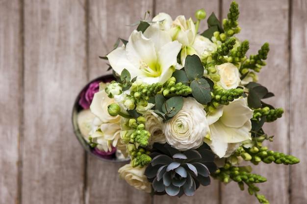 Bukiet z białych róż i soczysty widok z góry na drewniane tła. prezent dla mamy lub kobiety, praca kwiaciarni, dekoracje ślubne, koncepcja sprzedaży pięknych bukietów