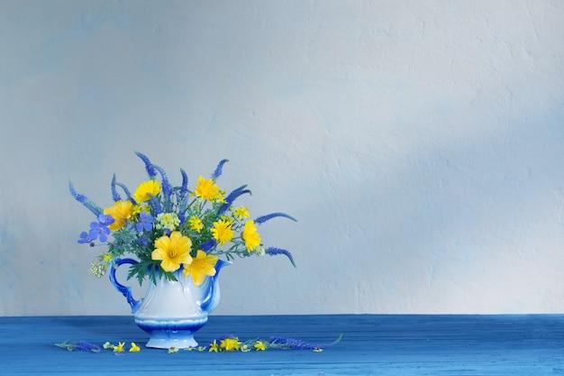 Bukiet z niebiesko-żółtych kwiatów w imbryku na drewnianym stole
