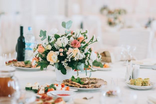 Bukiet z róż, eustomy i liści eukaliptusa. kwiatowa dekoracja ślubna. stół weselny ozdobiony świeżymi kwiatami.