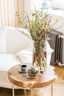 Bukiet zielonych gałązek w szklanym wazonie w skandynawskim wnętrzu na drewnianym stole