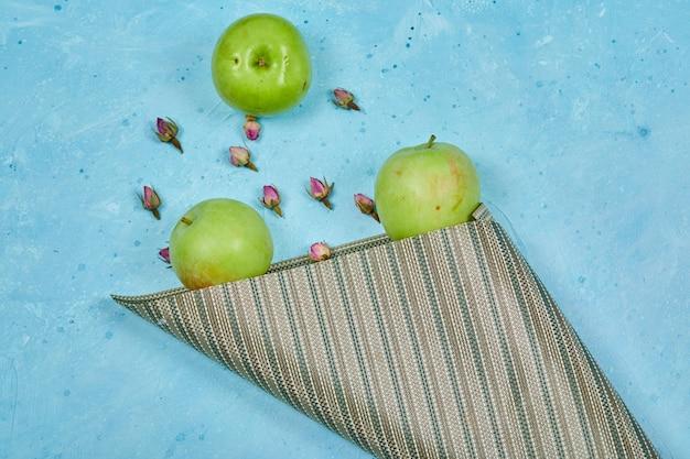 Bukiet zielonych jabłek z kwiatami na niebieskiej powierzchni.