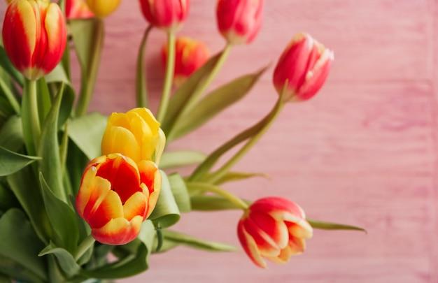 Bukiet żółci, czerwoni i różowi tulipany na różowej drewnianej tło kopii przestrzeni.