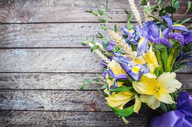 Bukiet żółto-fioletowych kwiatów, irys na drewnianym