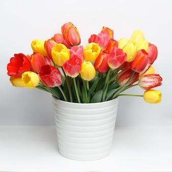 Bukiet żółtych i czerwonych tulipanów stojących w białym dużym wazonie