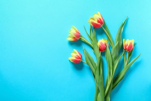 Bukiet żółtych i pomarańczowych tulipanów na jasnoniebieskim tle