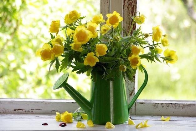 Bukiet żółtych kwiatów w konewce