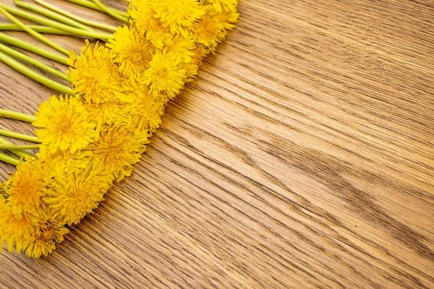 Bukiet żółtych mniszek na tle drewna, letnia jasna kompozycja, baner