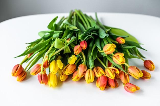 Bukiet żółtych, pomarańczowych i czerwonych tulipanów. białe tło. widok z góry. skopiuj miejsce