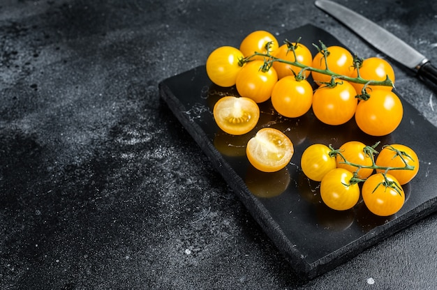 Bukiet żółtych pomidorów cherry na marmurowej desce. czarne tło. widok z góry. skopiuj miejsce.