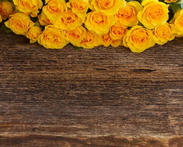Bukiet żółtych róż z miejsca na kopię na drewnianym