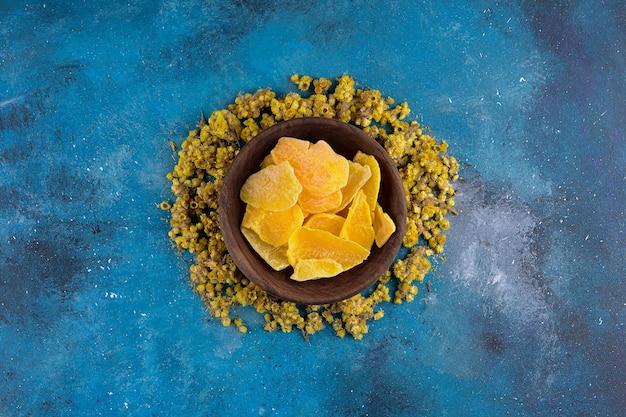 Bukiet żółtych suszonych kwiatów i suszonych owoców na niebieskim stole.