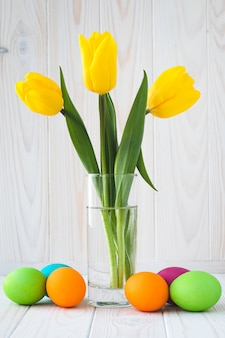 Bukiet żółtych tulipanów i kolorowych pisanek na jasnym tle drewnianych. paschalny kartkę z życzeniami z wiosennych kwiatów.