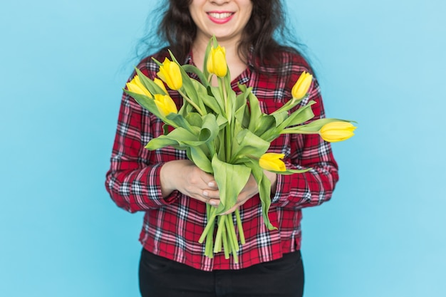 Bukiet żółtych tulipanów na rękach kobiety na niebieskiej ścianie