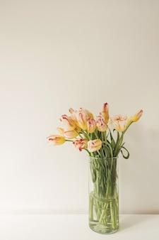 Bukiet żółtych tulipanów w szklanym wazonie na białej ścianie.