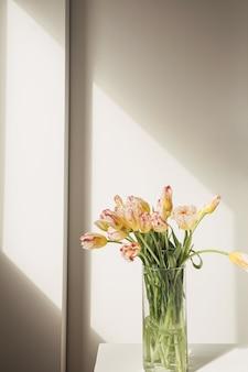 Bukiet żółtych tulipanów w szklanym wazonie na białej ścianie