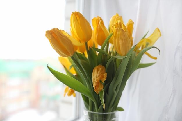 Bukiet żółtych tulipanów w wazonie na parapecie. prezent na dzień kobiety z żółtych kwiatów tulipanów. piękne żółte kwiaty w wazonie przy oknie.
