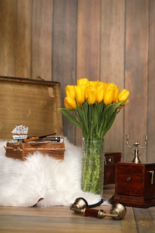 Bukiet żółtych tulipanów w wazonie we wnętrzu pokoju retro. retro wnętrze z bukietem tulipanów stary telefon i walizka.