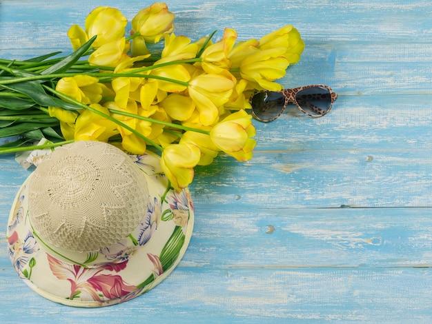 Bukiet żółtych tulipanów z kapeluszem i szkłami na błękitnym drewnianym stole.