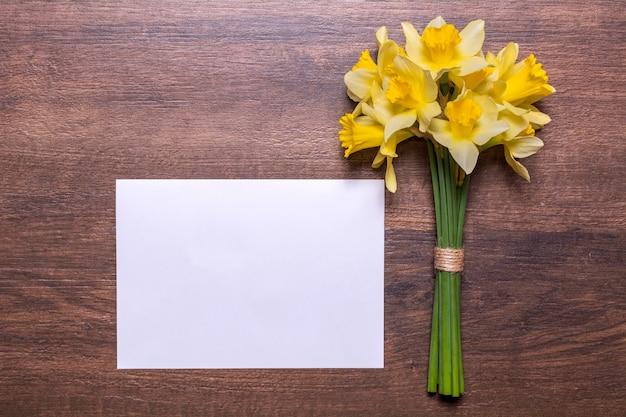 Bukiet żonkili i kartka białego papieru na drewnianym tle. wiosenne żółte kwiaty. papier z miejscem na tekst. płaska konstrukcja, widok z góry.
