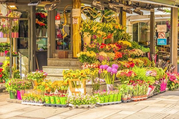 Bukiety kolorowych kwiatów przy wejściu do kwiaciarni.