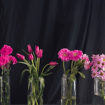 Bukiety różowe kwiaty w wazonach