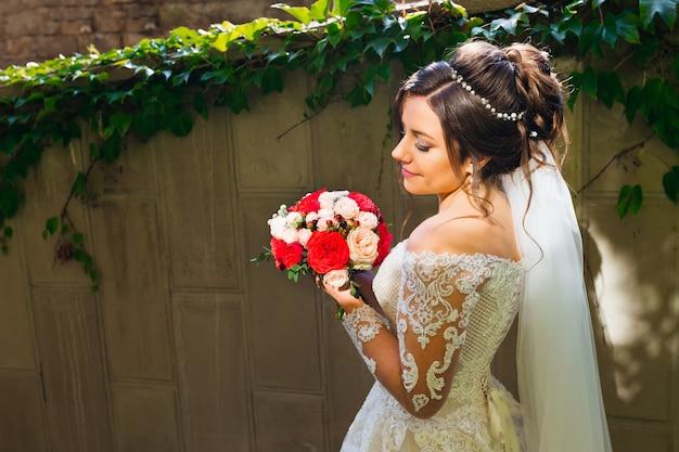 Bukiety ślubne w rękach panny młodej. piękna fryzura i makijaż. biała sukienka i welon ślubny