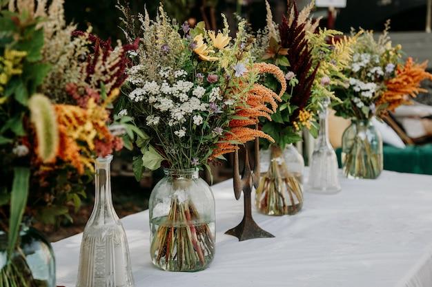 Bukiety w stylu rustykalnym na stole w szklanych wazonach i słoikach