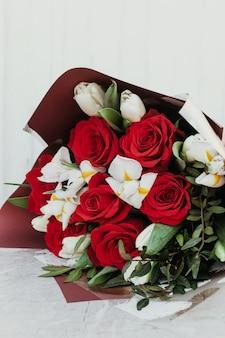 Bukiety z różnych kwiatów czerwonych róż i białych.
