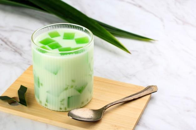 Buko pandan to słodkie jedzenie wykonane z galaretki i soku pandan z perłami sago i rozdrobnionym miąższem kokosowym ze śmietaną lub mlekiem. podawane na szklanym, białym tle tabeli z miejsca na kopię.